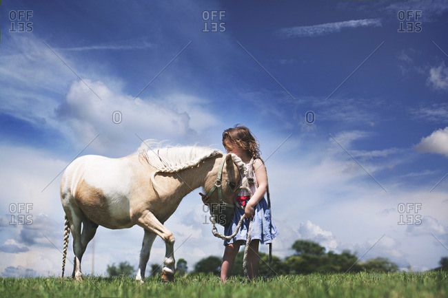 Little girl standing in a field with her pet miniature horse