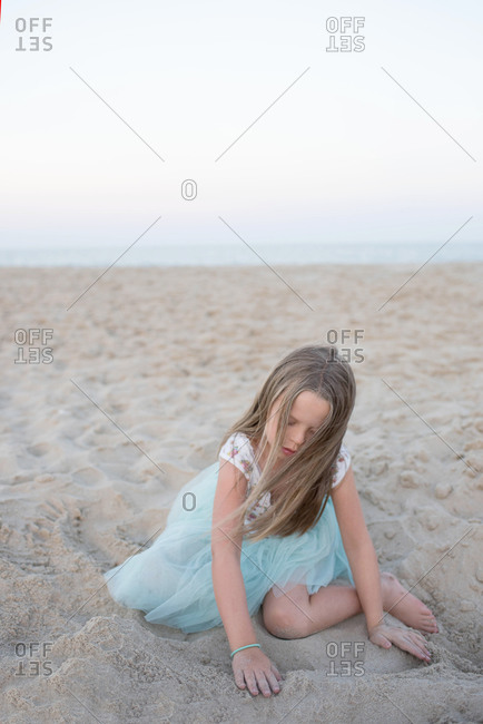 Young girl playing in the sand at the beach