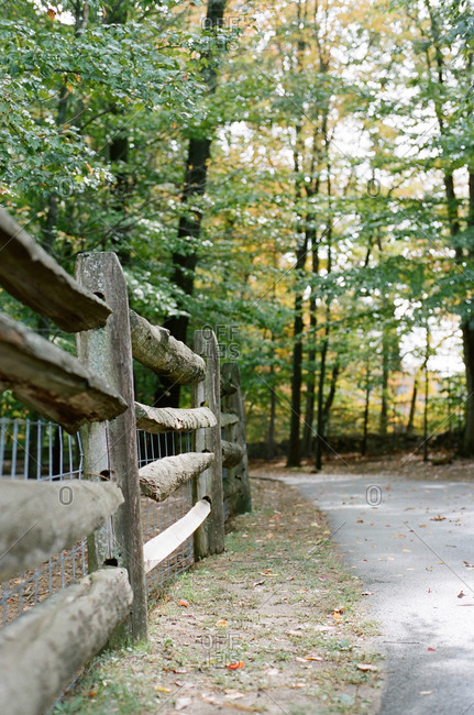 Wood, split rail fence along a wooded path