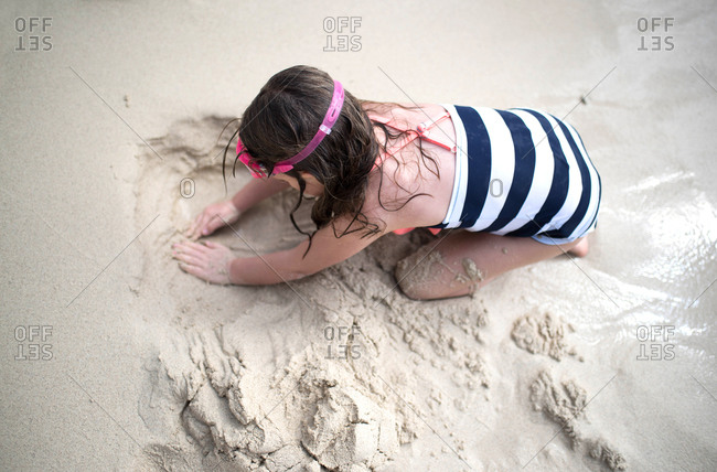 Young girl in a striped swimsuit digging in the sand at the beach