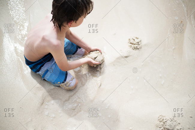 Young boy in striped swim trunks digging in the sand at the beach