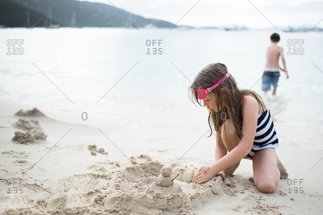 Young girl in a striped swimsuit playing with sand at the beach