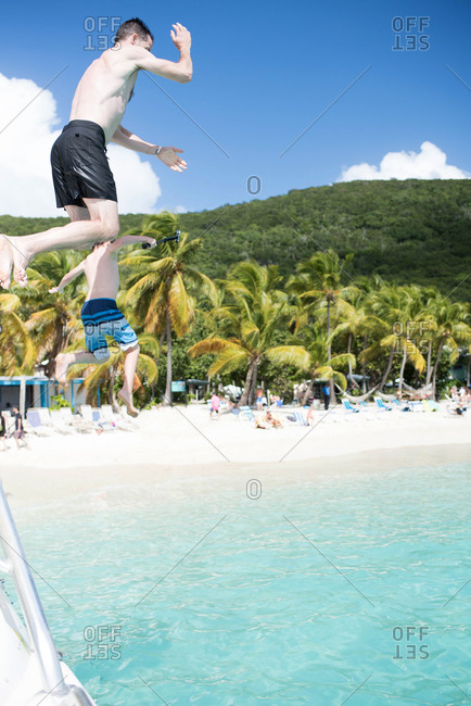 Father and son jumping into the water along a tropical beach