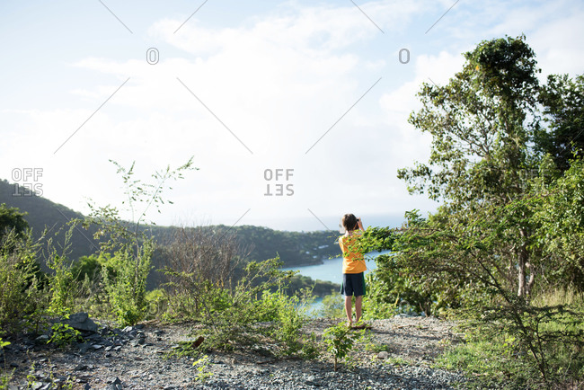 Boy taking a photo with his digital tablet from a tropical island hillside