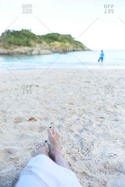 View of a woman's bare feet resting on a sandy beach
