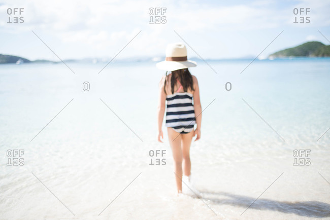 Young girl in a striped swimsuit walking into the water along a beach