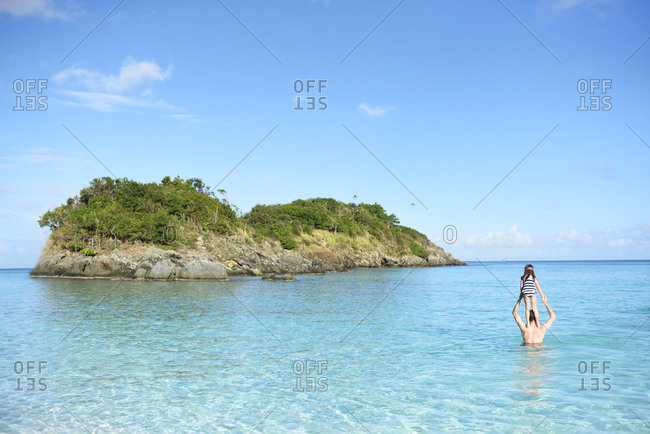 A father wading in tropical island waters while supporting his daughter on his shoulders