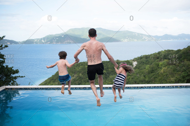 A father and his two children holding hands and leaping into a resort swimming pool together