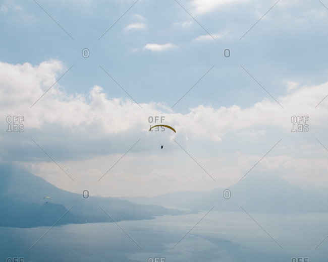 Paragliders gliding over a scenic coastal mountain range