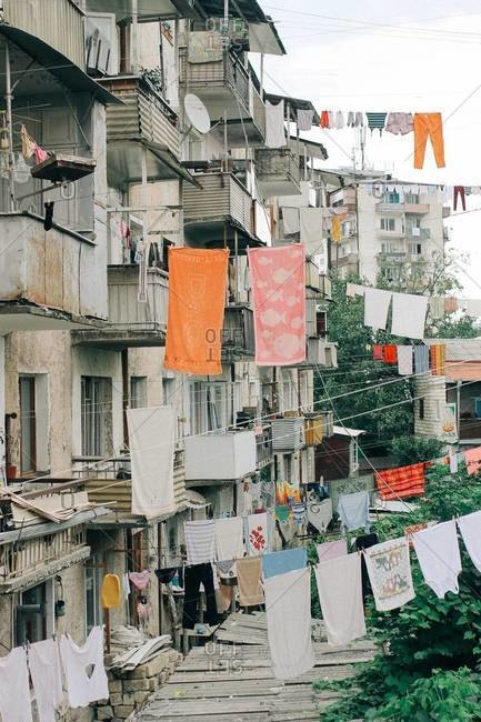 Clotheslines strung from apartment balconies in an urban area