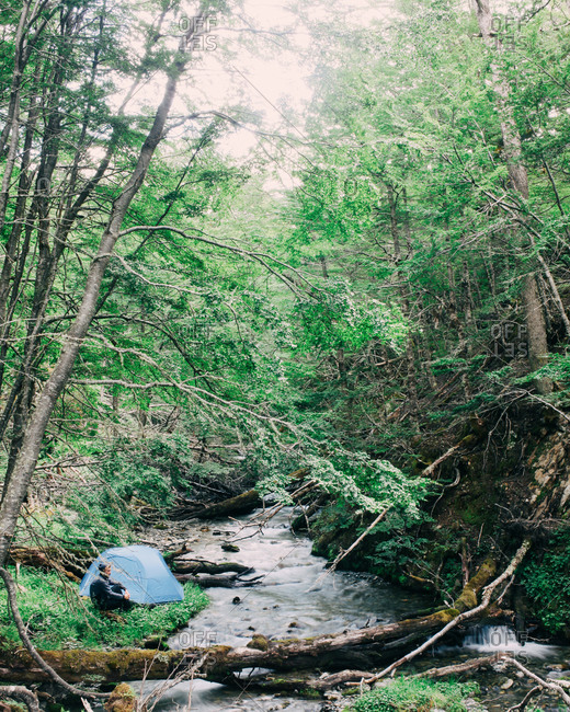 Man sitting next to a tent pitched alongside a wooded stream