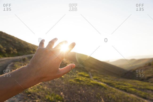 Hand reaching towards the sun at sunset