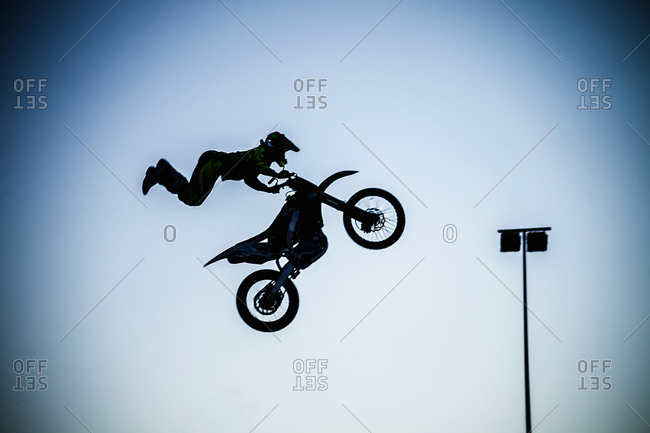 Man performing extreme stunt with motorcycle in mid air
