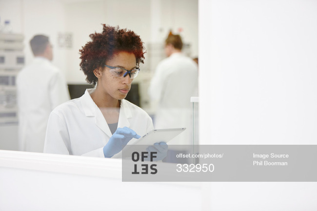 Female scientists working in laboratory with tablet