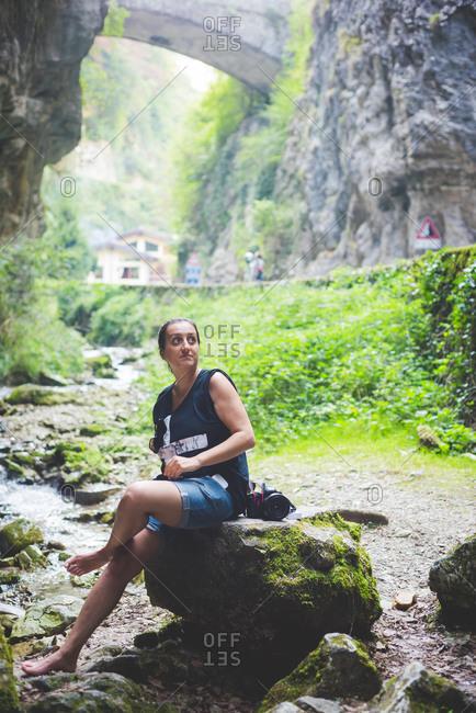 Woman sitting on rock in stream, rock hills and stone bridge in background, Garda, Italy