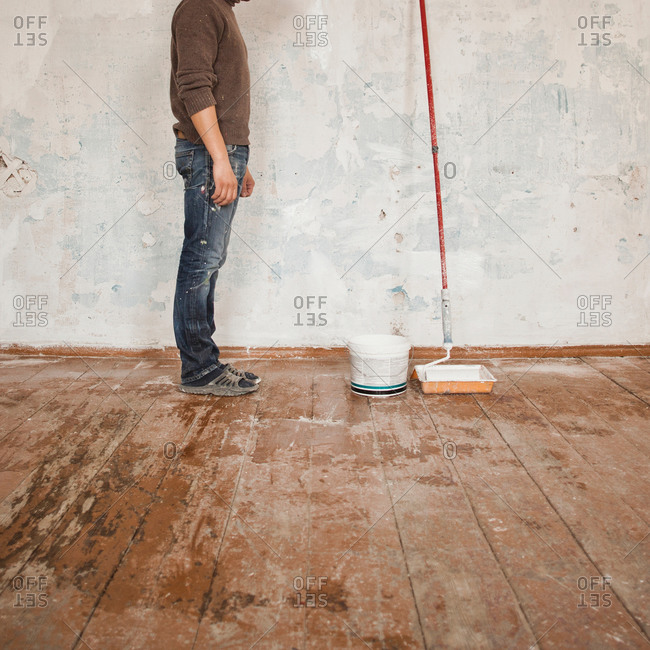 Mid adult man standing in room next to paint and paint roller, low section