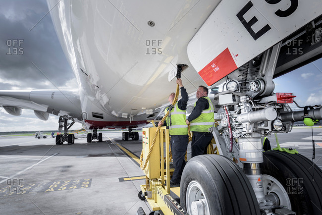 Ground crew affixing loading equipment on an aircraft