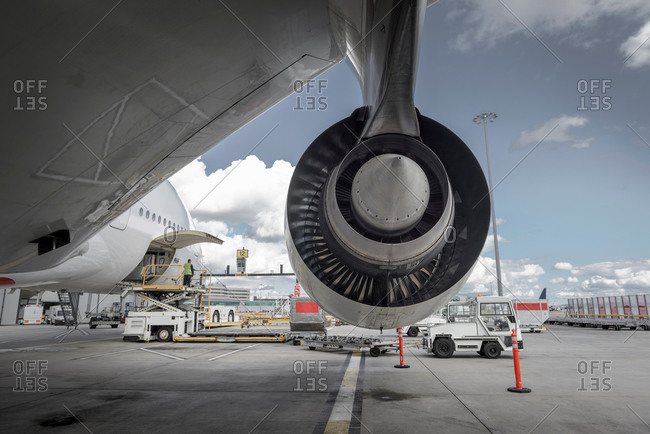 Rear view of an jet engine with ground crew loading freight