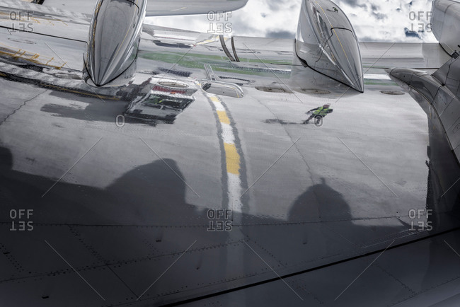 Reflection of ground crew in wing of an aircraft