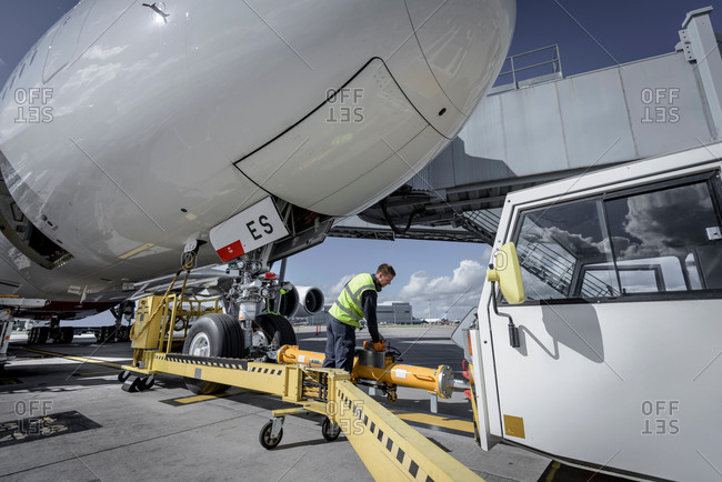 Ground crew attaching tow bar to an aircraft