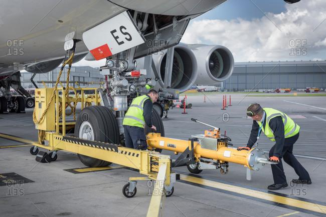 Ground crew fixing tow bar onto an aircraft at an airport