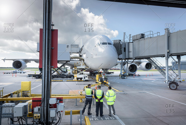 Ground crew inspecting an aircraft on stand in an airport