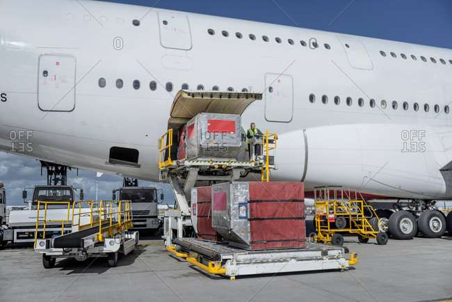Ground crew loading freight and luggage into an aircraft