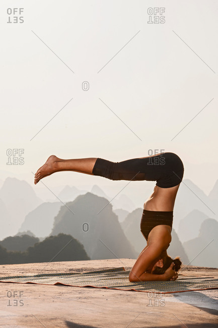 Profile of woman in headstand yoga pose above limestone mountains, Yangshuo, Guangxi Zhuang, China
