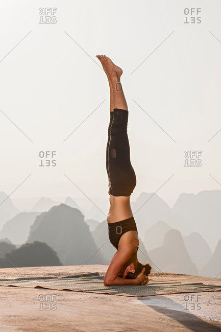Side view of woman in headstand yoga pose above limestone mountains, Yangshuo, Guangxi Zhuang, China