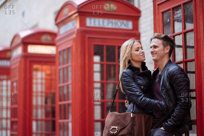Romantic young couple next to red phone boxes, London, England, UK