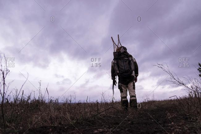 Rear view of male hiker hiking in empty landscape, Ural, Russia