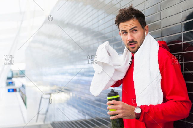Sweating young male runner leaning against tiled wall drinking water