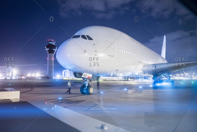 Engineer communicating with pilot of an aircraft on runway at night