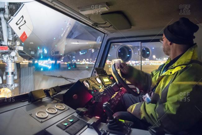 Tug driver moving an aircraft on runway at night
