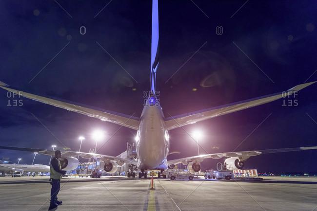 Rear view of an aircraft on runway at an airport at night