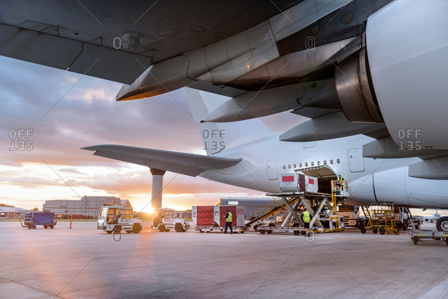 Ground crew loading an aircraft at sunrise