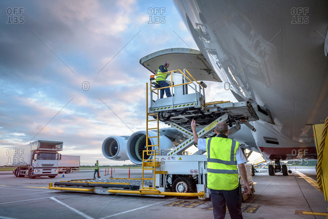 Ground crew attending to an aircraft with freight loader at an airport