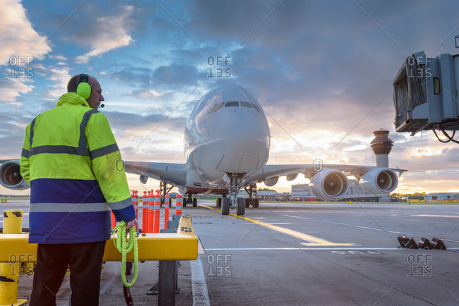 Chief engineer watching an aircraft arrive at stand in an airport