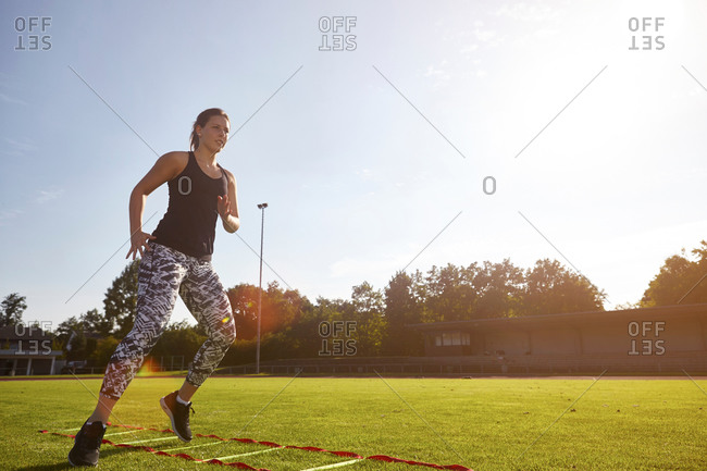 Young woman training on agility ladder on grass