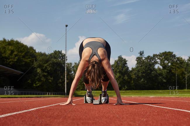 Young female runner bending forward on race track starting line
