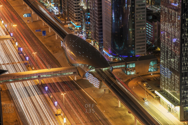 High angle view of city highway and Dubai metro rail station at night, downtown Dubai, United Arab Emirates