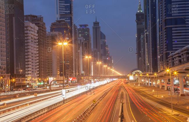 City highway and Dubai metro rail station at night, downtown Dubai, United Arab Emirates