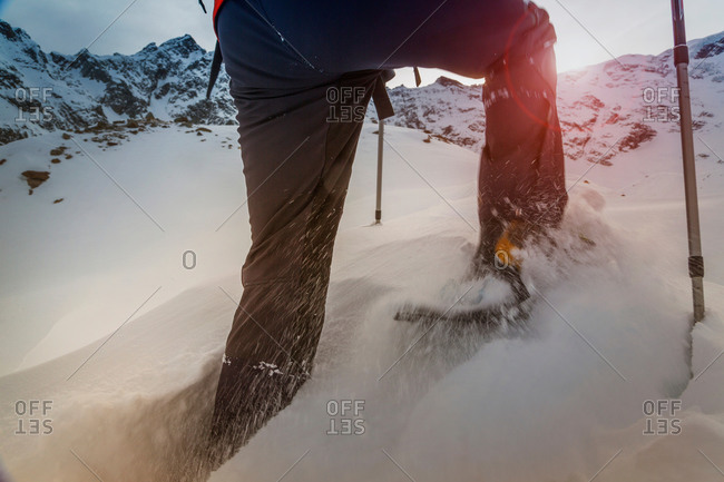 Climber wearing snow shoes walking through deep snow, Monte Rosa, Piedmont, Italy