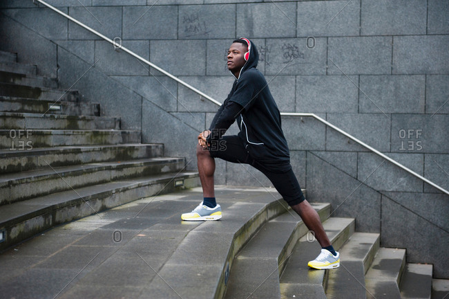 Young man exercising stretching legs on steps outdoors