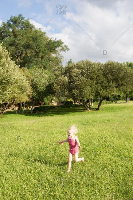 Female toddler wearing bathing suit running in field