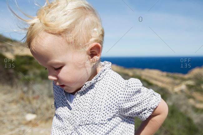 Female toddler looking down at coast, Calvi, Corsica, France