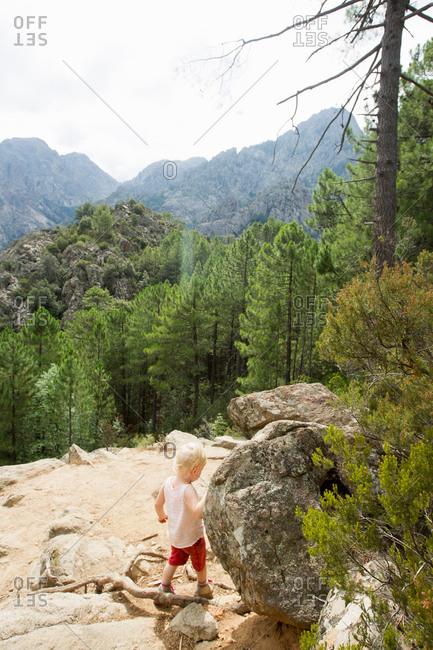 Female toddler exploring mountain rocks, Calvi, Corsica, France