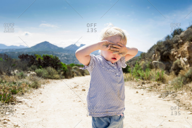 Female toddler on dirt track with hands covering eyes, Calvi, Corsica, France