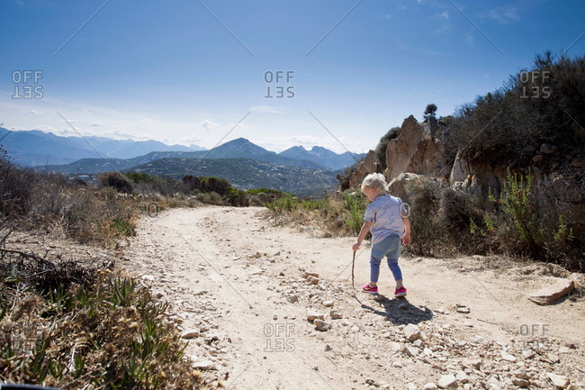 Female toddler on dirt track with walking stick, Calvi, Corsica, France