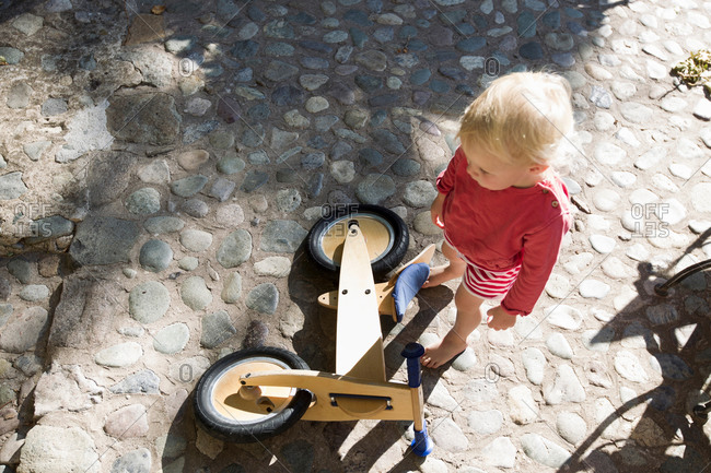 Overhead view of female toddler and wooden bicycle on cobbles